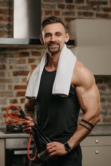 Un uomo muscoloso felice con un asciugamano bianco sulle spalle posa con la corda elastica nel suo appartamento