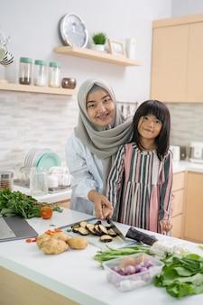 Felice donna asiatica musulmana con sua figlia che cucinano insieme in cucina
