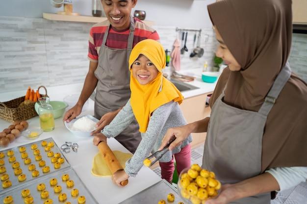 Felice famiglia musulmana con l'hijab che prepara la torta nastar insieme a casa. bella attività di cucina per genitori e figli per eid mubarak