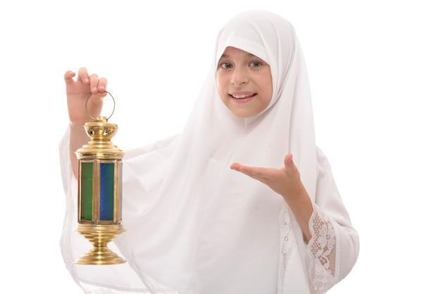 Ragazza musulmana felice che celebra il ramadan che tiene una lanterna festiva tradizionale