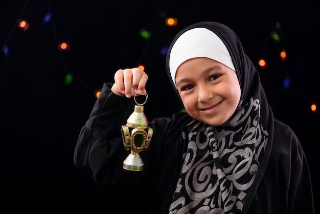 Ragazza musulmana felice che celebra con la lanterna del ramadan