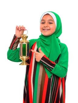 Ragazza musulmana felice che indica alla lanterna di ramadan