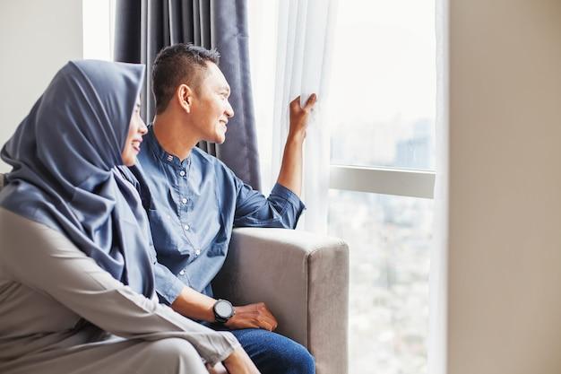 Felice coppia indonesiana musulmana che guarda nella finestra