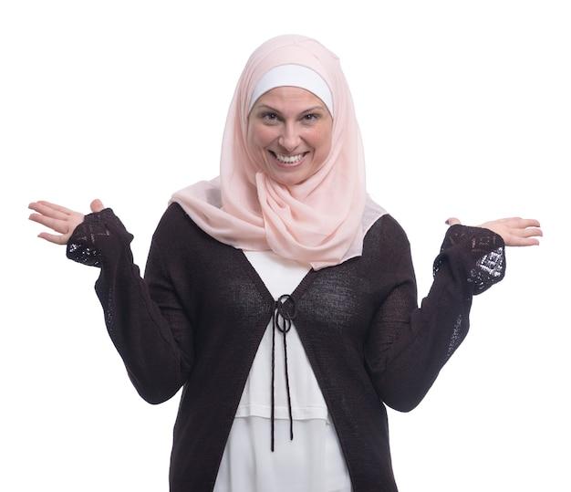 Felice donna musulmana che gode del successo sul muro bianco