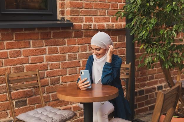 Felice donna musulmana che ha una videochiamata su smartphone in città