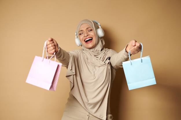 Felice donna musulmana in hijab con le cuffie che ascolta la musica e balla con i sacchetti di carta colorati nelle sue mani godendo le prossime festività religiose