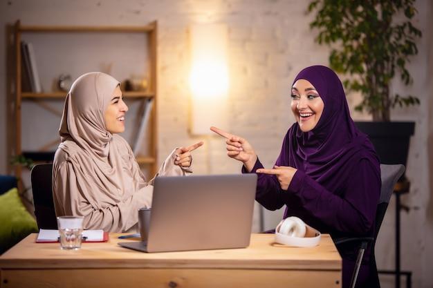 Felice donna musulmana a casa durante la lezione online. tecnologie, educazione a distanza, concetto di etnia