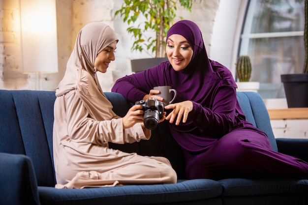 Felice donna musulmana a casa durante la lezione online.