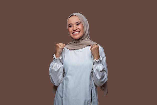 Felice donna musulmana in posa per celebrare il successo alzando le mani
