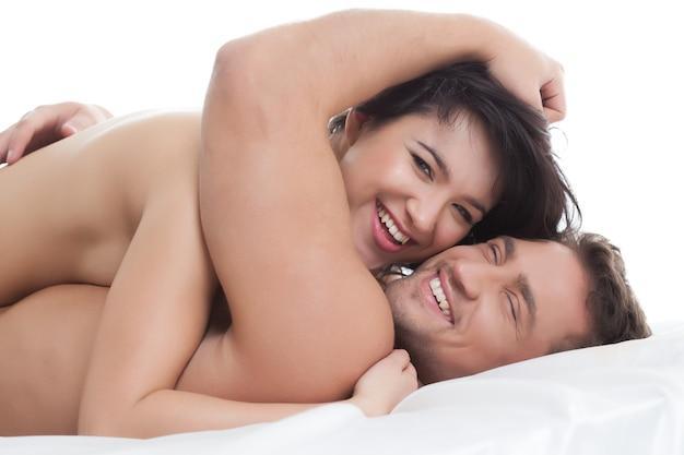 Amanti nudi felici che abbracciano sdraiato a letto, primo piano