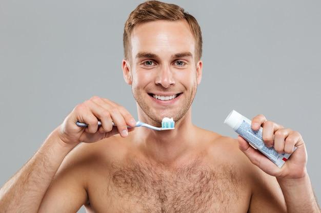 Felice giovane nudo che pulisce i denti con spazzolino e dentifricio