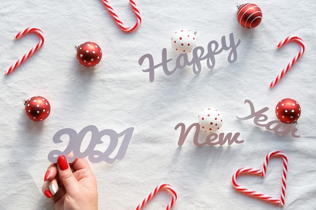 Testo di felice anno nuovo 2021. addobbi natalizi: cuori di bastoncini di zucchero, ninnoli bianchi rossi