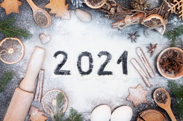 Felice anno nuovo 2021 scritto sulla farina. rami di albero di natale, biscotti di panpepato, spezie e prodotti da forno sulla superficie di legno nero