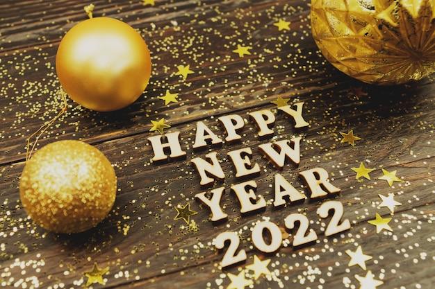 Il testo del buon anno 2022 su fondo di legno ha circondato i giocattoli dorati di natale e il ramo di un albero di pelliccia. cartolina d'auguri festiva per le vacanze