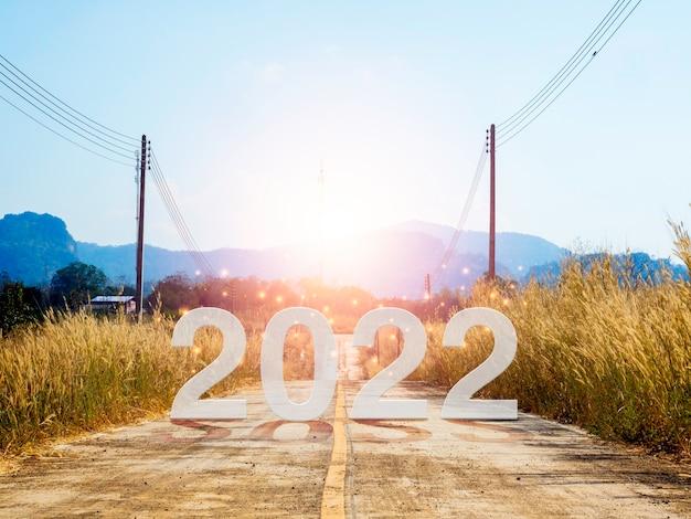 Felice anno nuovo 2022 con lettere grandi sulla strada aperta locale, dirigiti verso la grande montagna all'alba per superare gli ostacoli, il successo, il futuro, l'inizio e l'inizio con il concetto di obiettivo aziendale.
