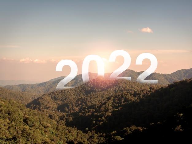 Felice anno nuovo 2022 con lettere grandi sulle montagne fertili e verdi lussureggianti e cielo blu, bella vista con spazio copia, un concetto di successo. benvenuto, buon natale e felice anno nuovo nel 2022.