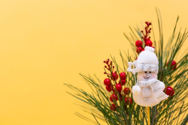 Felice anno nuovo sfondo bianco pupazzo di neve pallina di legno con rami di abete su uno sfondo pastello