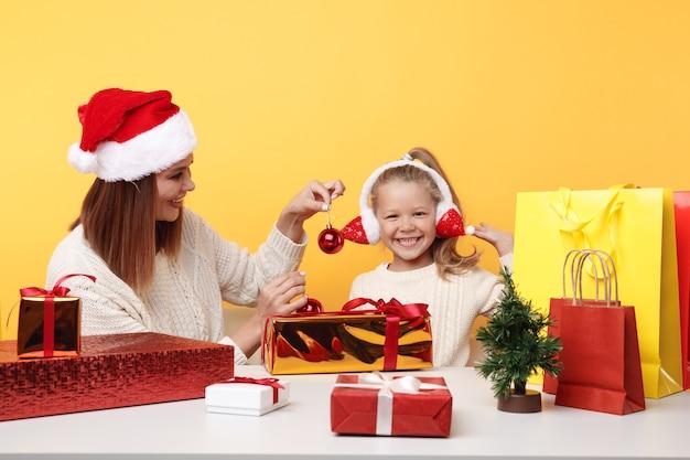Felice anno nuovo concetto. madre felice con bambino che si diverte insieme seduto alla scrivania con regali.