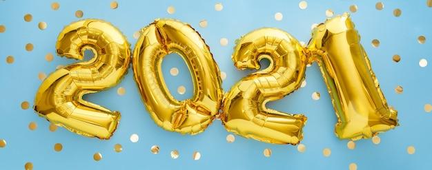 Palloncini in lamina d'oro di felice anno nuovo 2021 palloncino su blu con coriandoli.