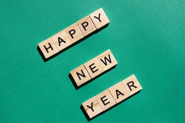 Le parole di auguri di felice anno nuovo sono disposte in lettere di legno