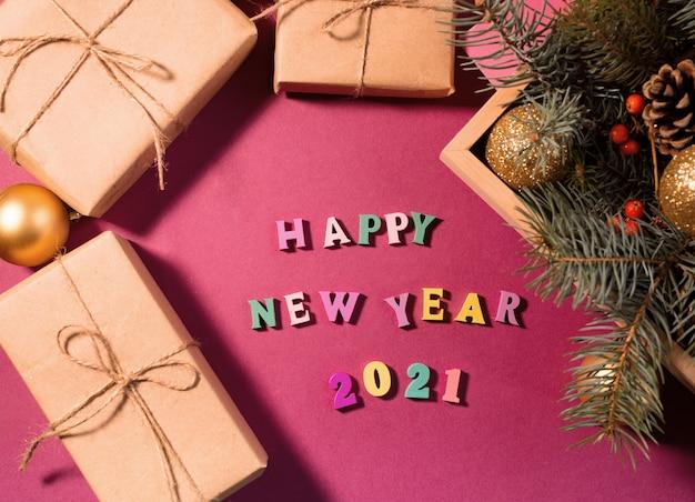 Felice anno nuovo saluto parole fatte di lettere in legno, scatole regalo su uno sfondo viola decorato con festosa rami di abete.
