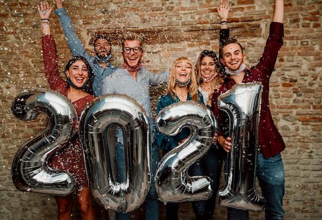 Felice anno nuovo! un gruppo di giovani che indossano una maschera per il viso per celebrare il 2021