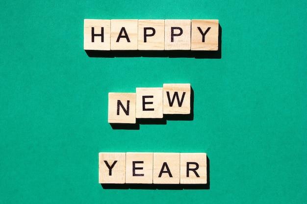 Felice anno nuovo - un'iscrizione fatta in lettere nere su blocchi di legno. sfondo verde.