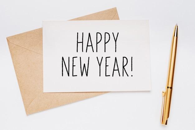 Nota di felice anno nuovo con busta e penna d'oro su sfondo bianco. buon natale e capodanno concept