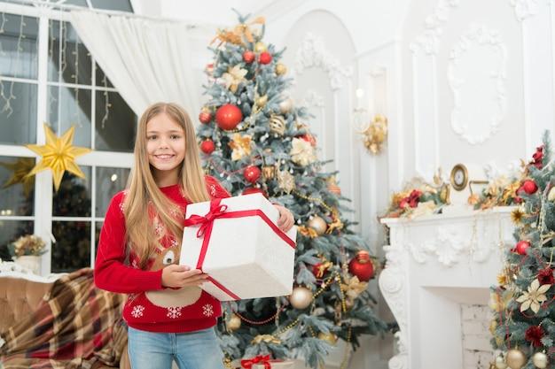 Buon anno. inverno. albero di natale e regali. acquisti online di natale. vacanza in famiglia. la mattina prima di natale. piccola ragazza. il bambino gode della vacanza. le nostre tradizioni.
