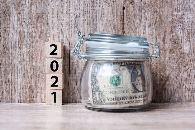 Felice anno nuovo con denaro dollaro americano vetro americano sulla tavola di legno