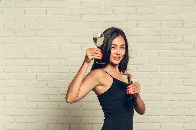 Buon anno a te. una donna giovane e bella che balla con un bicchiere di champagne