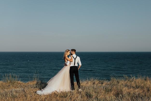 Coppia di sposini felici che abbracciano in riva al mare con il mare blu sulla superficie.