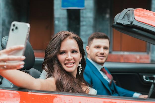 Gli sposi felici vanno alla celebrazione in un'auto rossa con il tettuccio scoperto. concetto di matrimonio