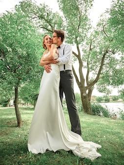 Sposi felici che abbracciano nel parco di primavera