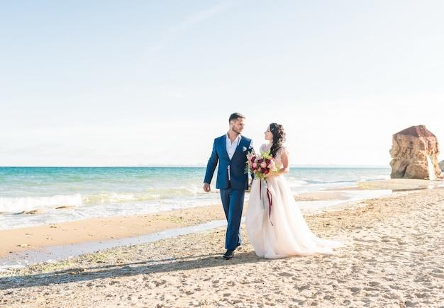 Sposi felici stanno mano nella mano sullo sfondo del mare blu. passeggiata di nozze su una spiaggia di sabbia. sullo sfondo il cielo blu