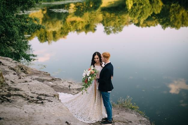 Sposi felici in piedi e sorridenti sulla riva del fiume