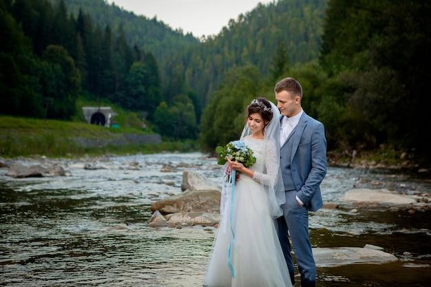 Sposi felici in piedi e sorridenti sul fiume. sposi in luna di miele, foto per san valentino.