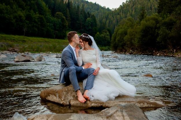 Sposi felici in piedi e sorridenti sul fiume