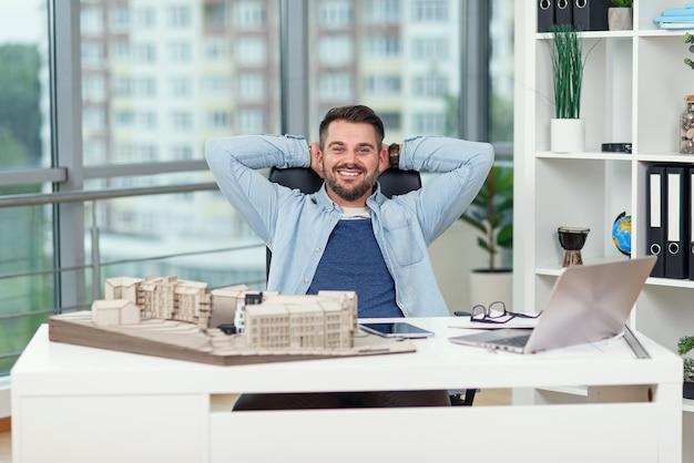 Felice ufficio lavoratore di sesso maschile in abiti casual ha appoggiato i piedi sul tavolo dell'area di lavoro mentre sognava di riposo o vacanze. l'architetto gioioso si rilassa sul posto di lavoro portando a termine con successo il suo progetto.