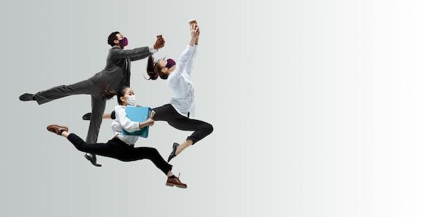 Impiegati felici con maschere facciali che saltano e ballano in abiti casual o abiti isolati in studio