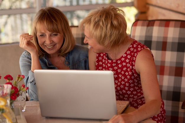 Felice vecchie signore che leggono la ricetta da internet tramite il portatile a casa