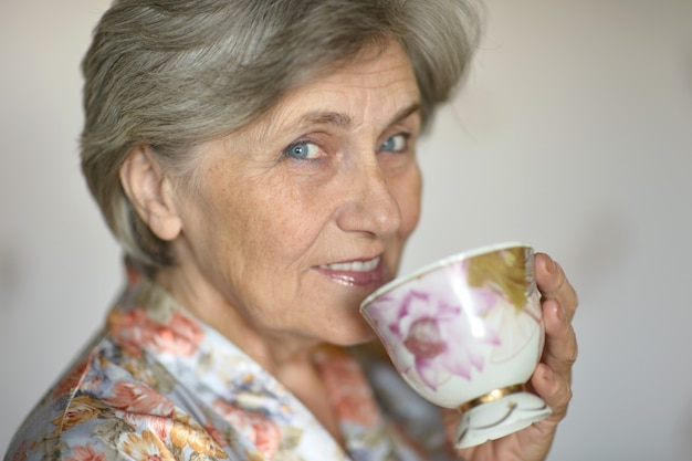 Felice anziana che beve il tè al mattino a casa