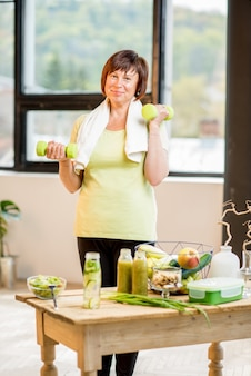Felice donna anziana in sport indossa allenamento con manubri al chiuso con cibo sano sul tavolo