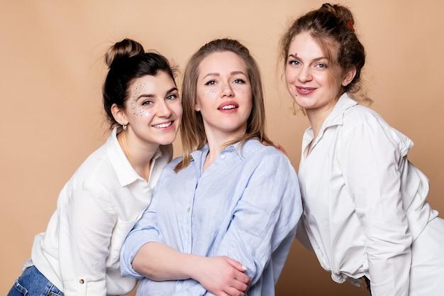 Donne multiculturali felici e sovrappeso in reggiseni isolati su beige. bellezza varia. tre signore multietniche avvolte in asciugamani da bagno in posa sorridenti alla telecamera su sfondo beige. ripresa in studio