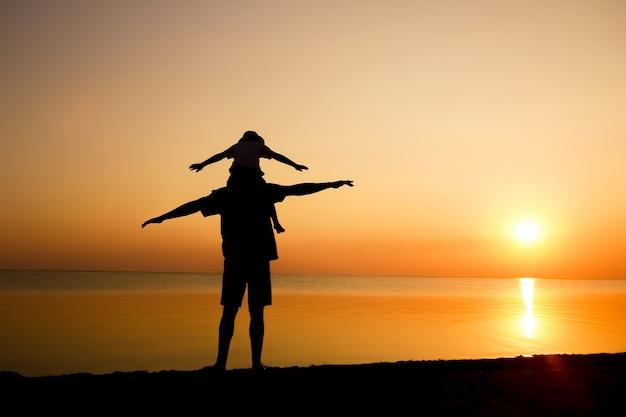 Un genitore felice con il bambino in riva al mare gioca sul viaggio della silhouette della natura