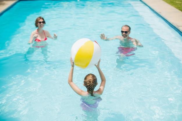 Genitori felici e figlia che giocano con la palla di nuoto in piscina