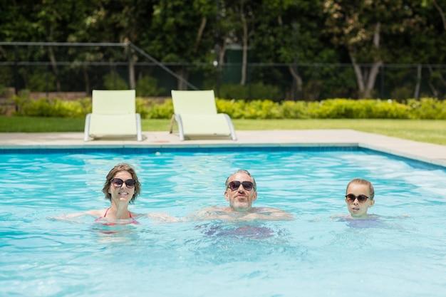 Genitori felici e figlia in piscina