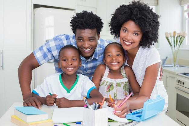 Genitori felici che aiutano i bambini a fare i compiti