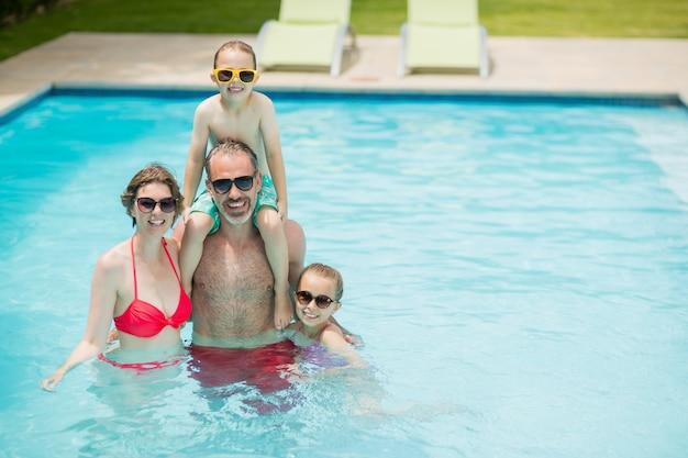 Genitori felici e bambini in piscina