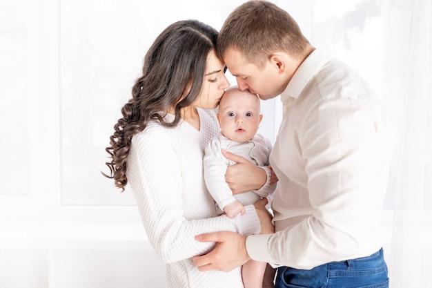 Genitori felici che baciano un bambino, concetto di famiglia felice